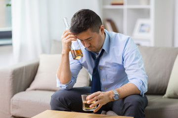 alcoholism, alcohol addiction and people concept - male alcoholic with bottle and glass drinking whiskey at home