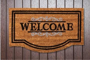 New welcome doormat on wooden floor
