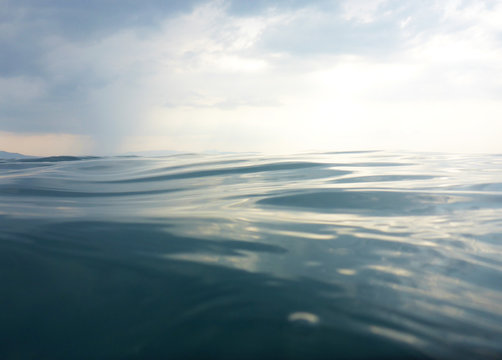 Background texture of clear, blue sea at water level and a cloudy evening sky