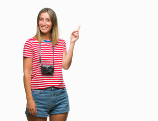Young beautiful woman taking pictures using vintage photo camera over isolated background with a big smile on face, pointing with hand and finger to the side looking at the camera.