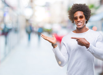 Afro american man wearing sunglasses over isolated background amazed and smiling to the camera while presenting with hand and pointing with finger.