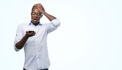Young african american man using smartphone stressed with hand on head, shocked with shame and surprise face, angry and frustrated. Fear and upset for mistake.