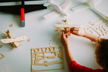 little boy making plane models from wood