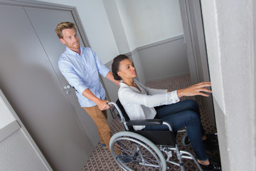 disabled woman on a wheelchair pushed by her boyfriend