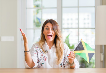 Young woman at home holding flag of Jamaica very happy and excited, winner expression celebrating victory screaming with big smile and raised hands
