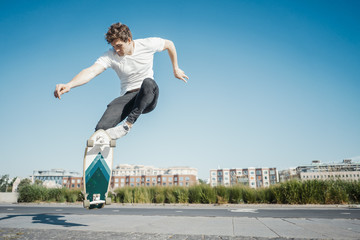 Young attractive man riding and jumping longboard in the park.
