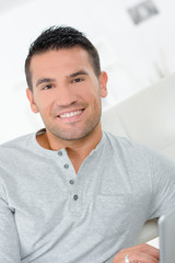 portrait of handsome young man smiling at home