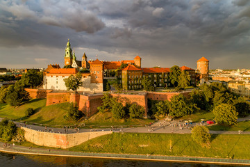 Poster Krakow Historic royal Wawel castle and cathedral in Cracow, Poland. Aerial view in sunset light with dark stormy clouds
