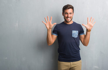 Handsome young man over grey grunge wall showing and pointing up with fingers number ten while smiling confident and happy.