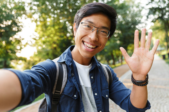 Smiling asian male student in eyeglasses making selfie and waving