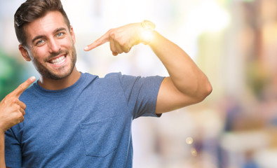 Young handsome man over isolated background smiling confident showing and pointing with fingers teeth and mouth. Health concept.