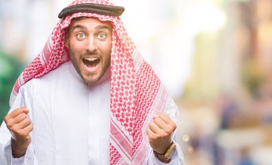 Young handsome man wearing keffiyeh over isolated background celebrating surprised and amazed for success with arms raised and open eyes. Winner concept.