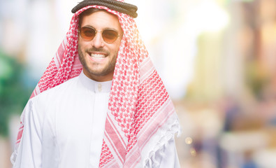 Young handsome man wearing keffiyeh over isolated background looking away to side with smile on face, natural expression. Laughing confident.