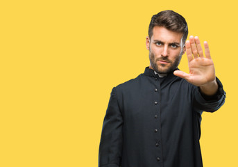 Young catholic christian priest man over isolated background doing stop sing with palm of the hand. Warning expression with negative and serious gesture on the face.