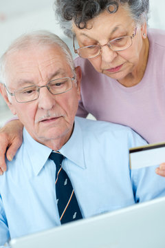 elderly couple using the card on the internet