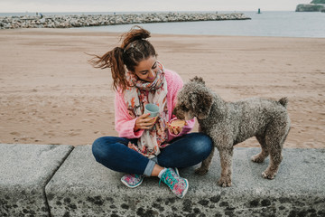 .Young woman wearing a pink sweater, playing with her adorable brown spanish water dog on the seafront of Gijon in the north of Spain on a cloudy summer day. Having fun, relaxed afternoon. Lifestyle