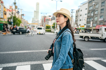 woman crossing the road and looking upward