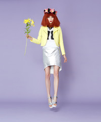 Red haired model posing in vintage dress holding a flower