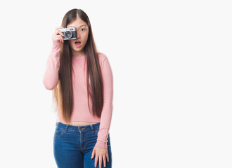 Young Chinese woman over isolated background taking pictures using vintage camera scared in shock with a surprise face, afraid and excited with fear expression