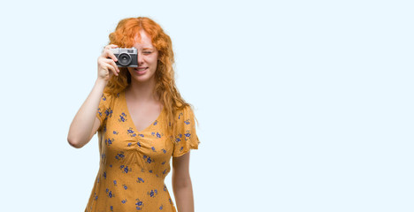 Young redhead woman taking pictures holding vintage camera with a happy face standing and smiling with a confident smile showing teeth