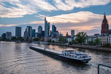 Frankfurter Skyline während des Sonnenuntergangs über dem Main, Blick auf das Bankenviertel, Transportschiff fährt über den Main