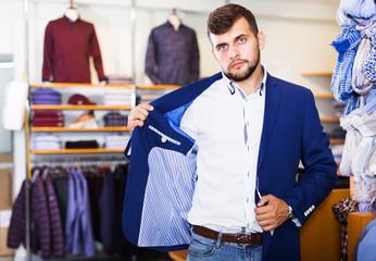 man choosing casual jacket in fashion store