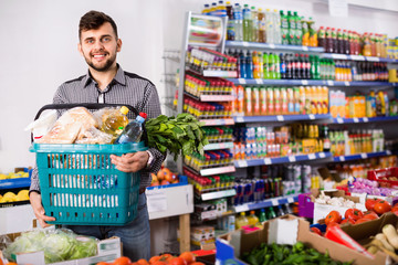 Portrait of guy with shopping basket filled food products in supermarket