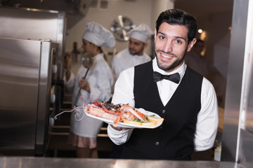 Waiter with seafood dish in kitchen of restaurant