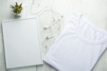 An empty folded T-shirt with a frame on a light background, for a design, a layout