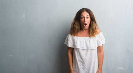 Middle age hispanic woman standing over grey grunge wall afraid and shocked with surprise expression, fear and excited face.