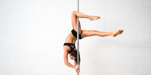 Young slim sexy pole dance woman in black lingerie on white wall background