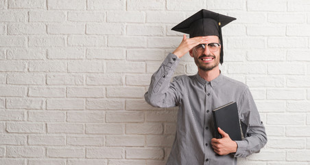 Young adult man over brick wall wearing graduation cap stressed with hand on head, shocked with shame and surprise face, angry and frustrated. Fear and upset for mistake.