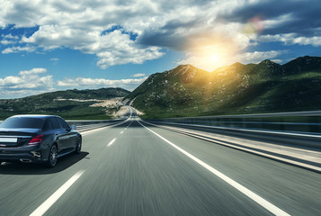 Black car rushing along a high-speed highway in the sun.