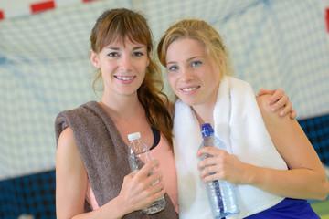 Sportswomen holding bottles of water