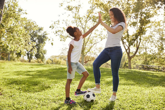 Mother And Daughter Playing Soccer In Park Together