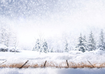 Winter christmas scenic background with copy space. Wooden flooring strewn with snow in forest and landscape with fir-trees covered with snow on nature.