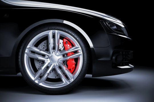 Sports car wheel with red brakes in studio lighting
