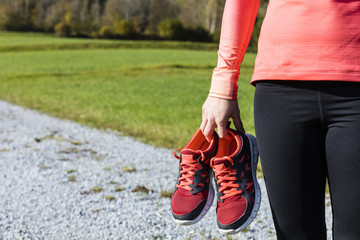 An athlete woman preparing for outdoors training with a shoe in her hand, Bavarian National Forest Park, Germany
