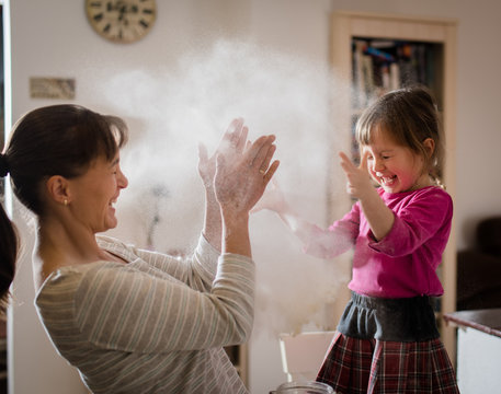 Mother with daughter having fun by baking