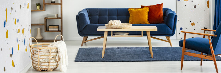 Panorama of wooden table in front of blue sofa in colorful flat interior with armchair. Real photo