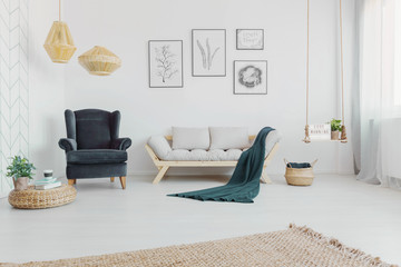 Real photo of a cozy living room interior with grey accents, armchair, sofa and blanket with art collection on a wall