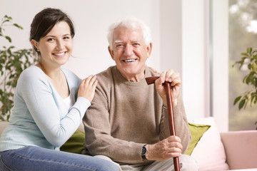 Happy senior man with walking stick and smiling granddaughter