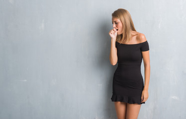 Beautiful young woman standing over grunge grey wall wearing elegant dress feeling unwell and coughing as symptom for cold or bronchitis. Healthcare concept.
