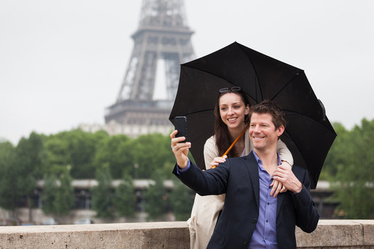 A Smiling Young Couple Take a Selfie Under an Umbrella with the Eiffel Tower behind Them