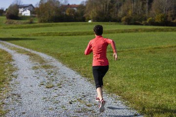 An athlete woman running outdoors, Bavarian National Forest Park, Germany