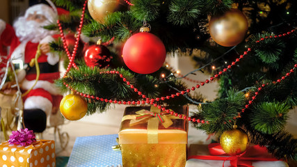 Beautiful winter holidays background with colorful gift boxes lying under Christmas tree