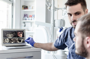 Male dentist and patient looking at x-ray