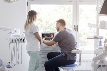 Male and female dentist looking at xray at clinic