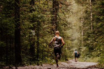 Fototapete - muddy runner athlete running forest autumn trail