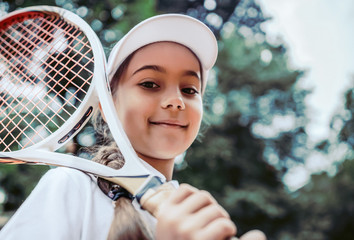Fototapeta Tennis training for young kid outdoors. Portrait of happy sporty little girl on tennis court. Caucasian child in white tennis sportswear on training. Sporty child girl looking in the camera. obraz